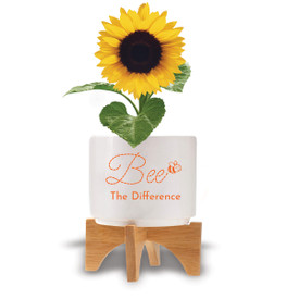 """Two-piece bamboo stand with modern white ceramic planter featuring the inspirational message """"Bee The Difference."""" Grows sunflowers."""