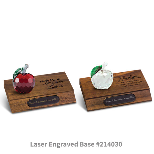 red and clear faceted crystal apples sitting on top of walnut laser engraved bases with black brass plates