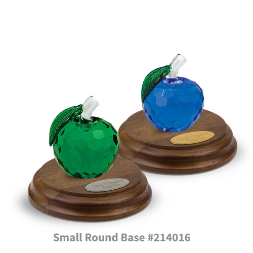 blue and green faceted crystal apples sitting on top of round walnut bases with brass and silver plates