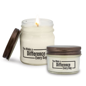 two white candle in glass jar with making a difference message
