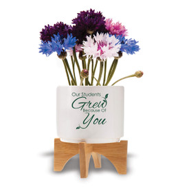 """Two-piece bamboo stand with modern white ceramic planter featuring the inspirational message """"Our Students Grew Because Of You."""" Grows a patriotic mix of flowers."""