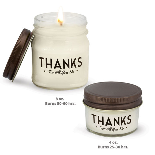 two white candles in glass jars with thanks message